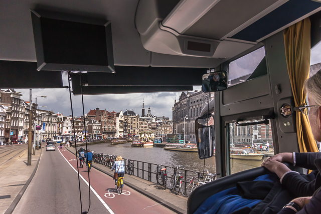Central Amsterdam through the windows of a bus.