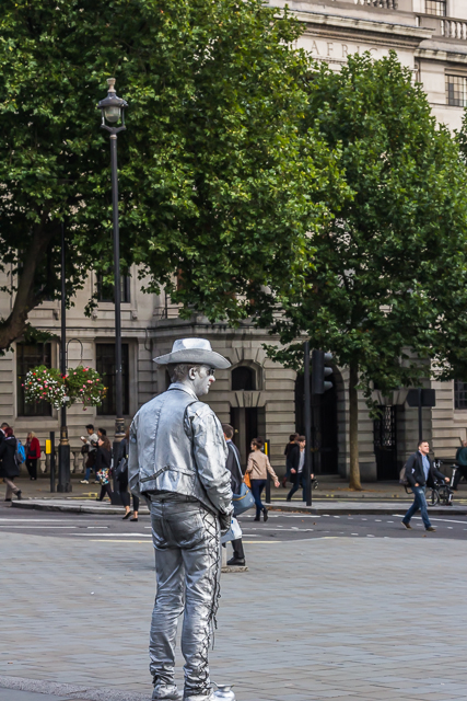A silver cowboy stands quietly at the edge of the square (near South Africa House) staring at the world passing by.