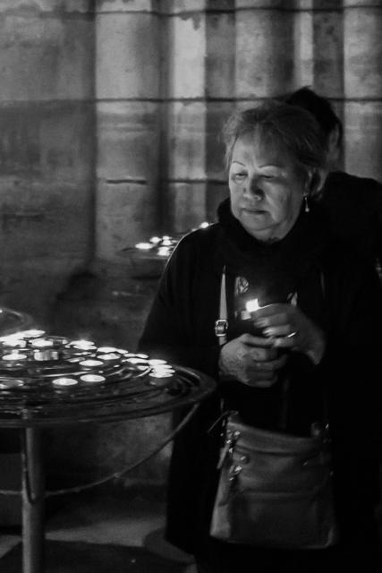 Lighting a prayer candle at Notre Dame de Paris.