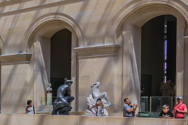 The horizontal crop of the right side of the original photo, emphasizing the body language of the people on the balcony viewing the nearby sculptures.