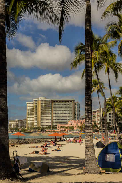 View of the Royal Hawaiian Hotel, aka the Pink Palace of the Pacific, from further down Waikiki Beach. The hotel is flanked by its own Royal Beach Tower on the right and the enormous Sheraton Waikiki on the left.