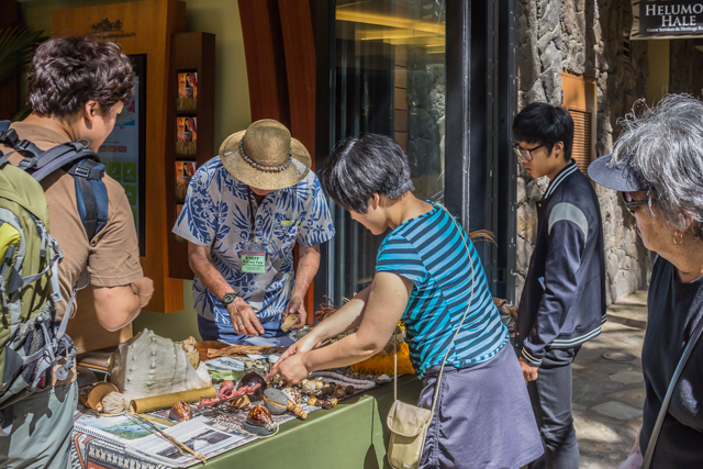 Visitors from Japan and Guam observe Upunu Tom  and his storytelling stuff at Helumoa Hale.