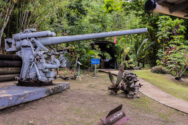 Japanese gun with a WWII era Quonset hut in the background.