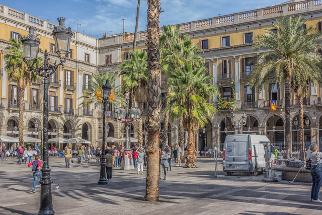 Placa Reial is just off La Rambla. A young Antoni Gaudi designed some of the lamposts in this square. There's one near the center of this photo. It's the one with the concrete base to the left of the palm trees. A woman is taking a picture of a snake wrapped around the pole.