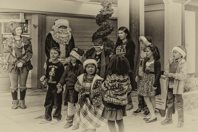 "A children's choir singing ""Rudolph the Red-nosed Reindeer"" in front of Santa and one of his elves."