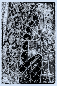 This closeup of one of the stained glass windows in the Church of the Twisted Columns (also known as Gaudi's Crypt)  with the cross motif on the right, the shards of mosaic tiles known as trencadis on the left and a metal mesh made from discarded needles from Güell's cotton mill covering the window. Many of the needles are reflected in the stained glass, emphasizing the space between them.