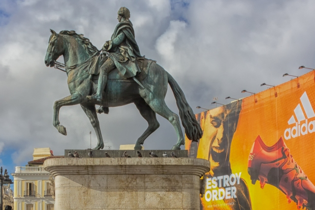 King Charles III rides above the middle of the square. That big billboard was selling a local beer when we first visited Puerta del Sol five years ago.